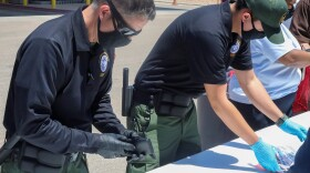 This May 4 photo provided by The U.S. Border Patrol shows U.S. Border Patrol Processing Coordinators help process and log personal items from migrants entering the Central Processing Center in El Paso, Texas.