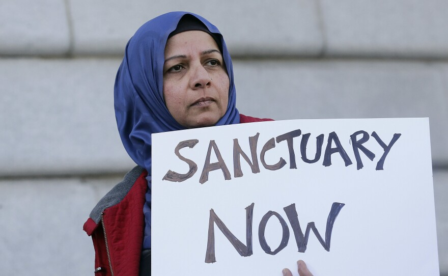 Protester Moina Shaiq holds a sign at a rally outside of City Hall in San Francisco. On Tuesday, a federal judge blocked a Trump administration order to withhold funding from sanctuary communities.