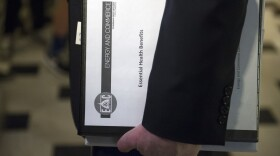 """House Energy and Commerce Committee Chairman Rep. Greg Walden, R-Ore., one of the stewards of the Republican health care legislation, carries a binder labeled """"Essential Health Benefits"""" as he leaves the Capitol Hill office of House Speaker Paul Ryan, March 24, 2017."""