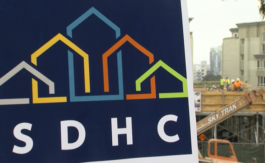The San Diego Housing Commission logo is seen in front of the construction site of a new apartment building for people recovering from homelessness, Sept. 4, 2018.
