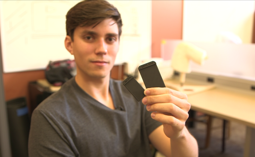 SDSU engineering student Spencer Koroly holds up rectangular plastic parts of his kneepad prototype, made from a 3-D printer.