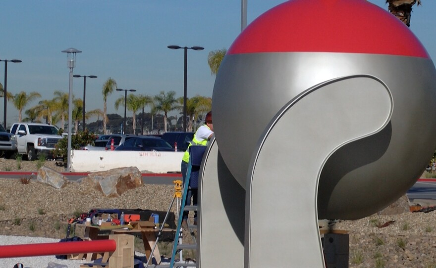A worker fine tunes the bottom of artist Christian Moeller's sculptures at the San Diego International Airport Rental Car Center, Dec. 9, 2015.