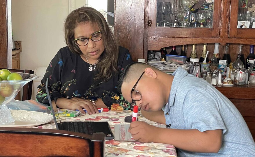 Alejandro Blanco, 13, does school work at the dining room table with help from his mother, Maria A. Lopez, Aug. 27, 2021. He went back to school this week as a freshman at Madison High School.