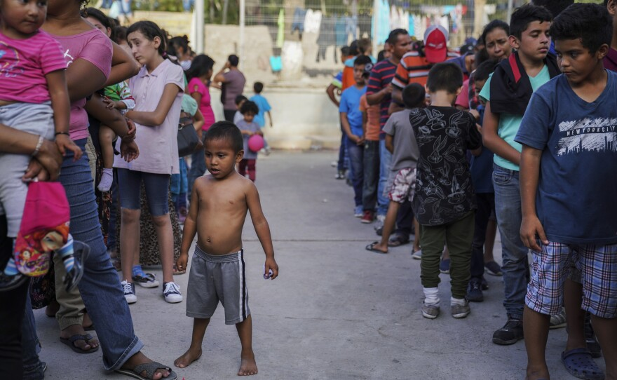 """In this Aug. 30, 2019 file photo, migrants, many who were returned to Mexico under the Trump administration's """"Remain in Mexico"""" program, wait in line to get a meal in an encampment near the Gateway International Bridge in Matamoros, Mexico."""
