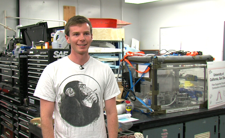 UCSD undergraduate Sam Avery stands in front of the triple-enclosed chamber he and his teammates built to contain small fires aboard a microgravity-simulating flight.