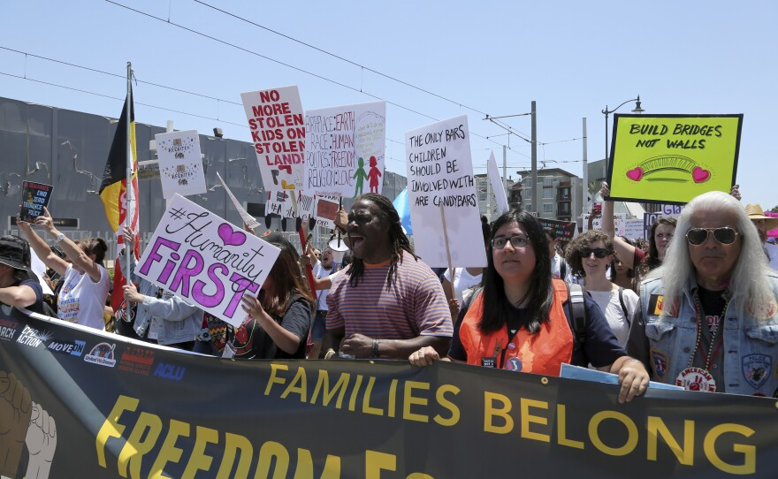"""Demonstrators hold signs as they participate in the """"Families Belong Together: Freedom for Immigrants"""" march on Saturday, June 30, 2018, in Los Angeles."""
