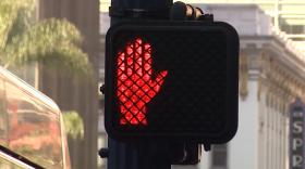A red hand illuminates on a pedestrian crosswalk light, Feb. 21, 2017.