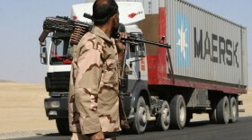 In this Oct. 27, 2010, file photo a private security contractor watches a NATO supply truck drive past in the province of Ghazni, south-west of Kabul, Afghanistan.