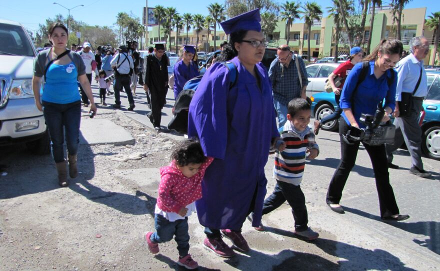 Angelica Lopez holds the hand of daughter, Ashley, and son, Osmar, as they and other immigrants and deportees approach the Otay Mesa Port of Entry where some plan to ask for asylum, March 10, 2014, Tijuana, Mexico.