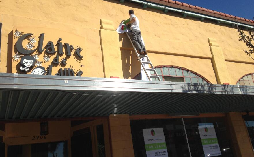A man hangs a for rent sign on the building that housed Claire de Lune, a popular North Park coffee shop, Feb. 17, 2016.