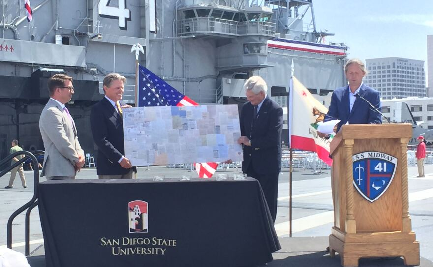 Andy Wiese (far right), SDSU history professor and chair of the history department, presents members of the USS Midway Museum Board with a collage of letters written by SDSU students during World War II, June 11, 2019.