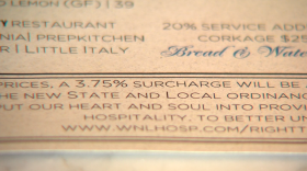 A note at the bottom of the menu at the Catania restaurant explains a new 3.75 percent surcharge to compensate for higher labor costs, Jan. 3, 2017.