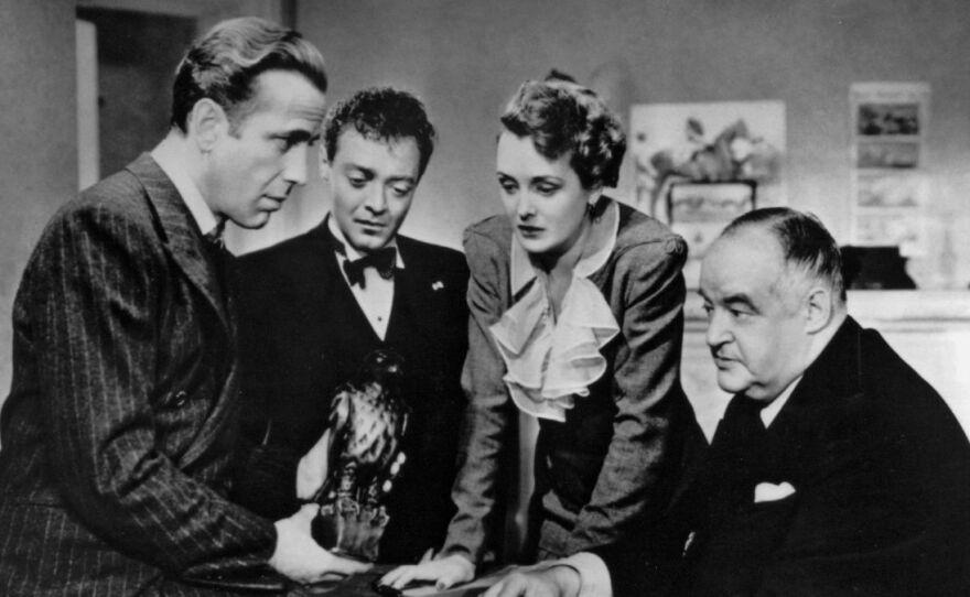 "Humphrey Bogart, Peter Lorre, Mary Astor, and Sydney Greenstreet admire the Black Bird at the center of John Huston's 1941 film adaptation of Dashiell Hammett's novel ""The Maltese Falcon."" The film screens on Jan. 28 as part of Film Geeks SD's Noir on the Boulevard year-long film series."
