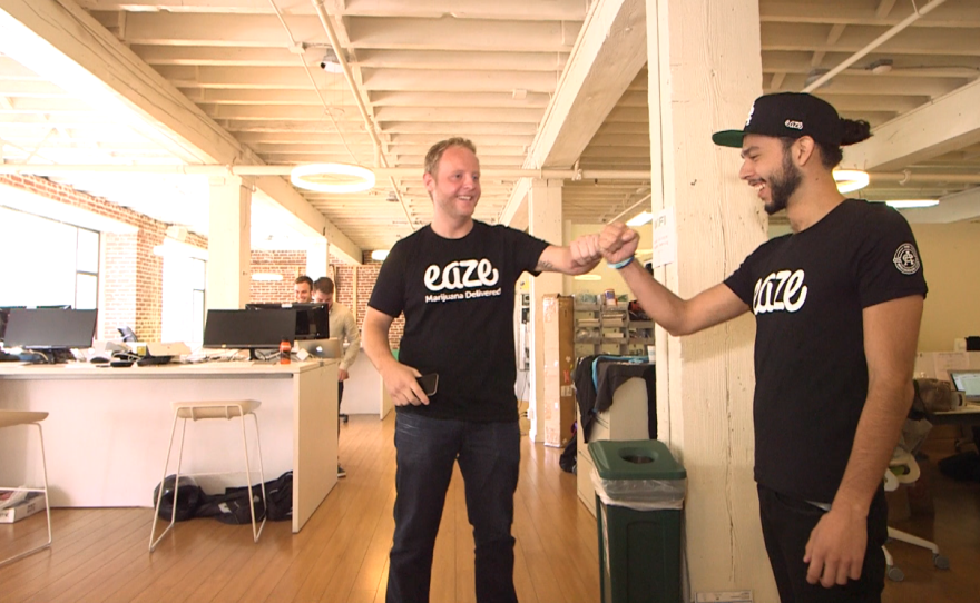 Eaze founder and CEO Keith McCarty gives a fist bump to an Eaze employee while riding around the company's San Francisco office on an electric floor scooter, Nov. 18, 2015.
