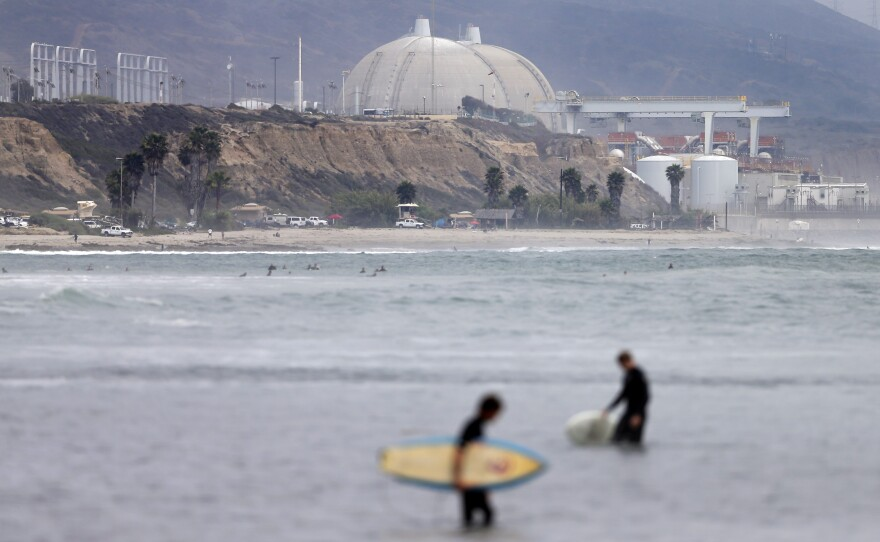 Surfers pass in front of the San Onofre nuclear power plant, June 7, 2013.