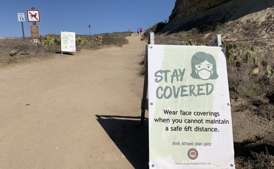 A sign warning people to wear masks due to COVID-19 at Torrey Pines State Beach, Feb. 26, 2021.