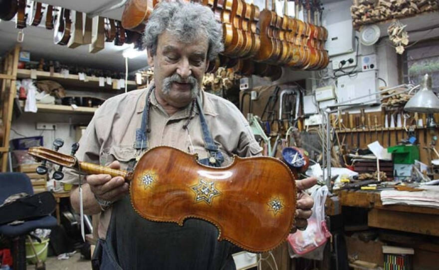 Violinmaker Amnon Weinstein in his Tel Aviv shop showing one of the restored Violins of Hope.