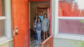 Nitin Bajaj and Nimisha Lotia stand with their kids inside the empty and damaged apartment unit where two tenants stayed without paying rent in Los Angeles, Calif., on Saturday, October 2, 2021.