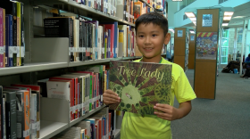 Nine-year-old Timothy Tang holds up his favorite book, Tree Lady, at the City Heights Weingart Library in San Diego on Friday August 10, 2018.