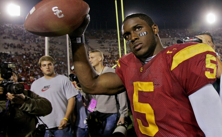 In this Nov. 19, 2005, file photo, Southern California tailback Reggie Bush walks off the field holding the game ball after the Trojans defeated Fresno State, 50-42, at the Los Angeles Coliseum.