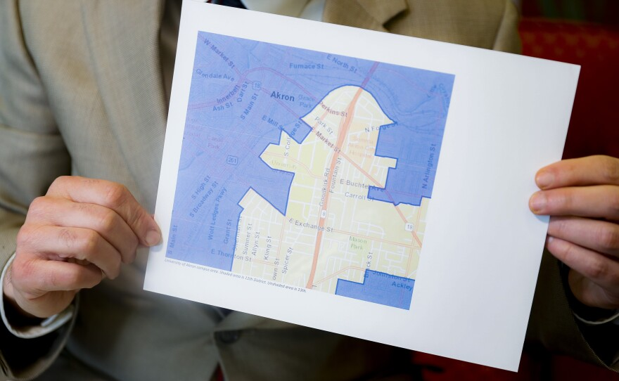 David Niven, a professor of political science at the University of Cincinnati, holds a map depicting a gerrymandered Ohio district.