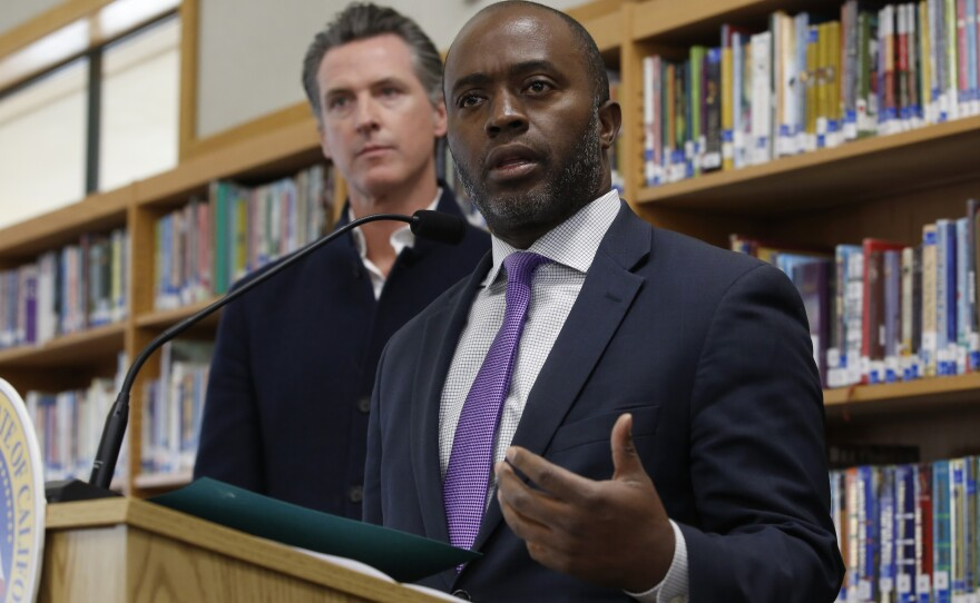 In this Oct. 31, 2019, file photo, state Superintendent of Public Instruction Tony Thurmond answers a reporter's question during a visit with California Gov. Gavin Newsom, background, to Blue Oak Elementary School, in Cameron Park, Calif.