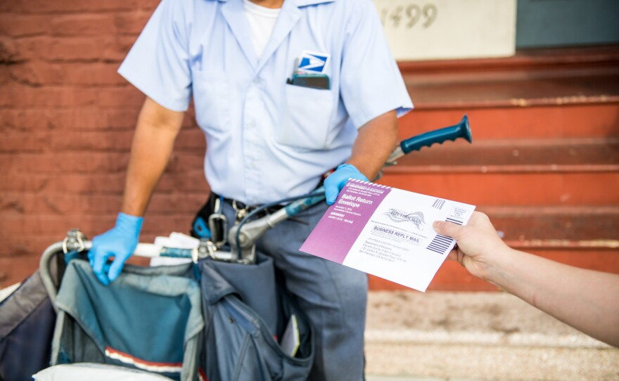 A San Francisco resident hands their mail-in ballot to U.S. Postal Service employee Elmer Padilla on Oct. 9, 2020.