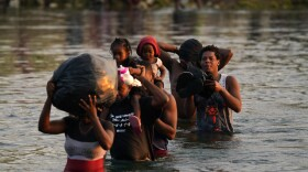 Migrants, many from Haiti, wade across the Rio Grande from Del Rio, Texas, to return to Ciudad Acuna, Mexico, Tuesday, Sept. 21, 2021, to avoid deportation from the U.S.