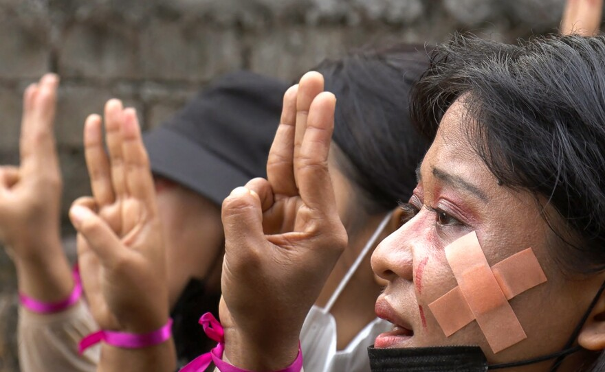 Protesters, wearing red makeup to simulate tears of blood, making the three-finger salute during a demonstration against the military coup in Hlaing Township, Yangon, Myanmar, on Thursday in a photo taken from a screenshot from AFPTV video.