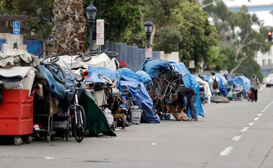 Homeless people stand among their items along 17th Street in San Diego, Sept. 19, 2017.