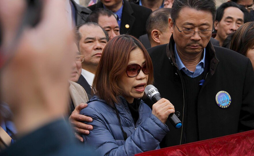 Peter Liang's mother speaks at the Feb. 20, 2016 protest in support of her son at Cadman Plaza in Brooklyn, N.Y.  while John Chan offers support.