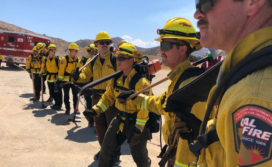 A CalFire hand crew prepares for a midday hike in 100-degree heat near Jamul on Aug 14, 2020.