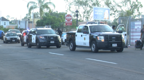 San Diego police cars with flashing lights roll up on 17th Street to clear the homeless and their tents from the sidewalks in the East Village, June 27, 2016.