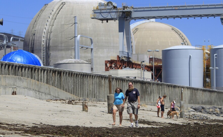 This June 30, 2011, file photo shows beach-goers walking on the sand near the San Onofre nuclear power plant in San Clemente.