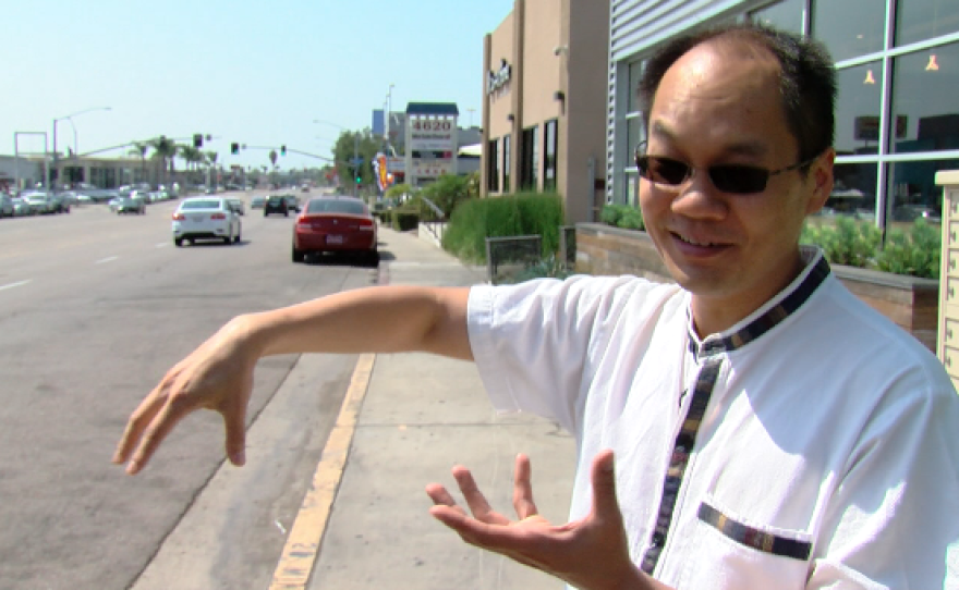 Ping Wang, one of the founders of the Convoy District Partnership, points out some of the best known restaurants on Convoy Street. Aug. 25, 2016.