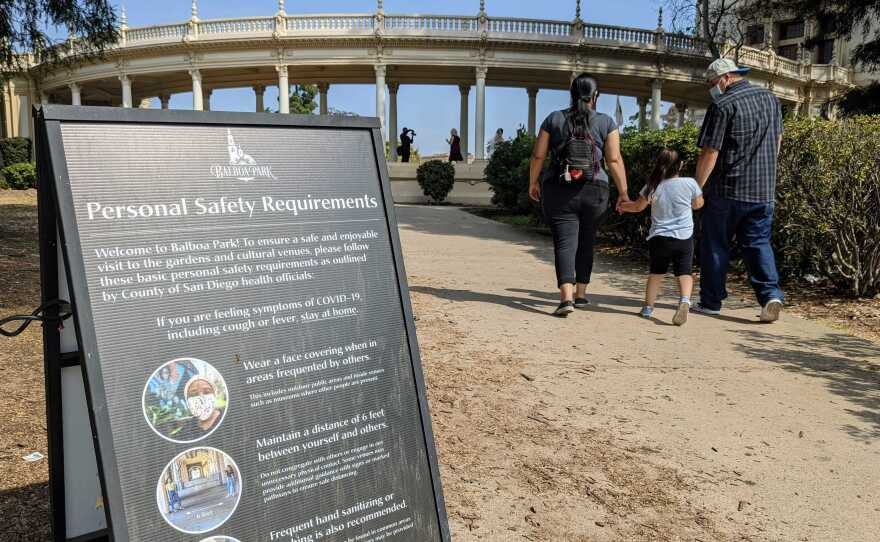 A COVID-19 safety guidelines sign at Balboa Park as a family walks in the background in this photo taken Oct. 23, 2020.