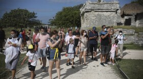 Tourists, required to wear protective face masks amid the new coronavirus pandemic, visit the Mayan ruins of Tulum in Quintana Roo state, Mexico, Tuesday, Jan. 5, 2021.