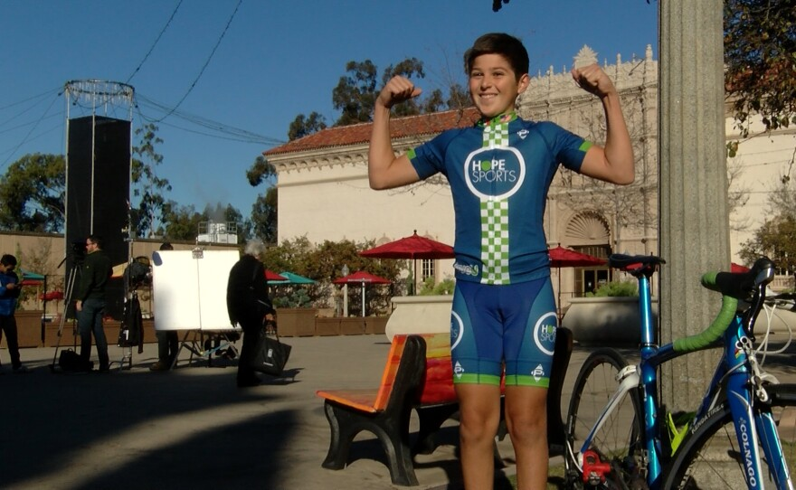 Bicycle racer Pablo Lozano, 13, shows excitement to watch the AMGEN Tour of California organizers film a promotional video at Balboa Park, Dec. 15, 2015.