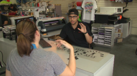 Christopher Avila working with a customer at T-Shirt Mart in Point Loma, March 11, 2015.