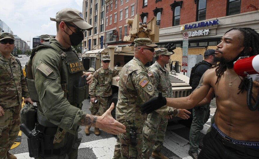 Demonstrator Aaron Covington shakes hands with National Guard troops and DEA police at a protest in Washington on Saturday over the death of George Floyd. President Trump announced that the National Guard forces would be pulling out of the nation's capital after several days of peaceful demonstrations.