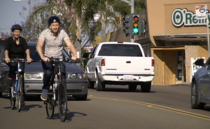 Bike Advisory Committee member Kathy Keehan and KPBS reporter Andrew Bowen bike along Garnet Avenue in Pacific Beach, April 21, 2017.