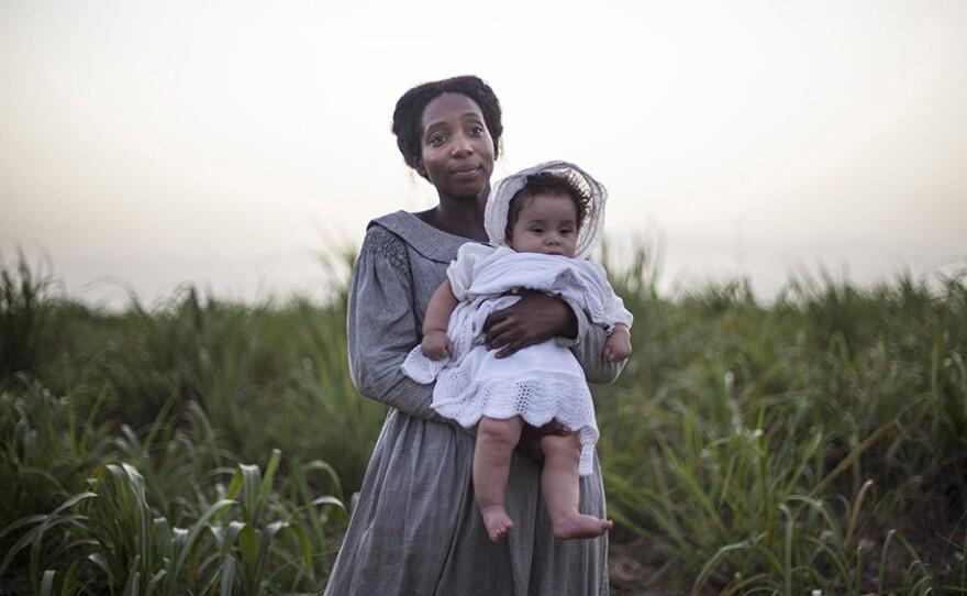 July (TAMARA LAWRANCE) holding a baby.
