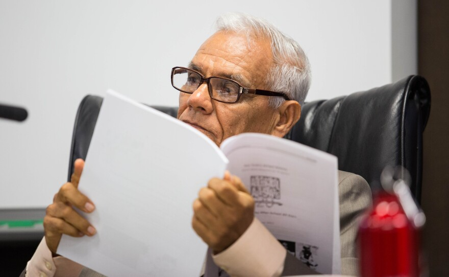 Rodolfo Linares reads a document presented to the San Ysidro School District board, July 9, 2015. He was elected to the board in 2014.