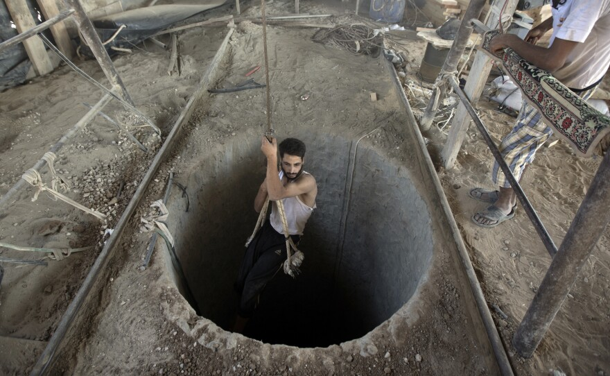 A Palestinian man is lowered into a smuggling tunnel that runs beneath the Egypt-Gaza Strip border, on Sept. 11, 2013. For the past year, Egyptian forces have cracked down on smuggling tunnels which Gazans used to import a wide range of goods, including weapons.
