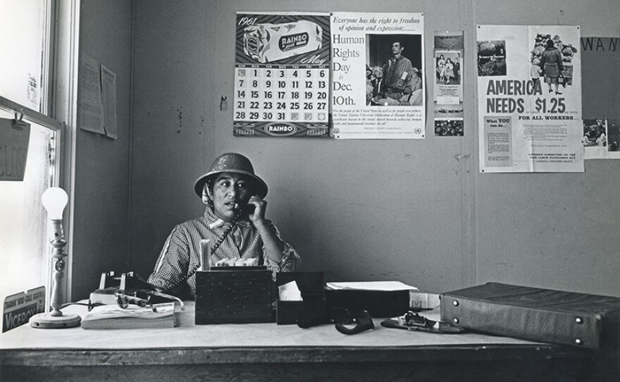 """Migrant mother Maria Moreno became the first farmworker woman in America to be hired as a union organizer. Wearing """"jungle"""" (safari) hat, Maria makes a phone call in the office of the Agricultural Workers Organizing Committee, Fresno, Calif. 1961."""