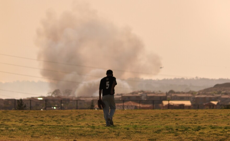 A baseball player walks to the outfield at Del Norte High School as the Bernardo Fire rages in the background. May 13, 2014.