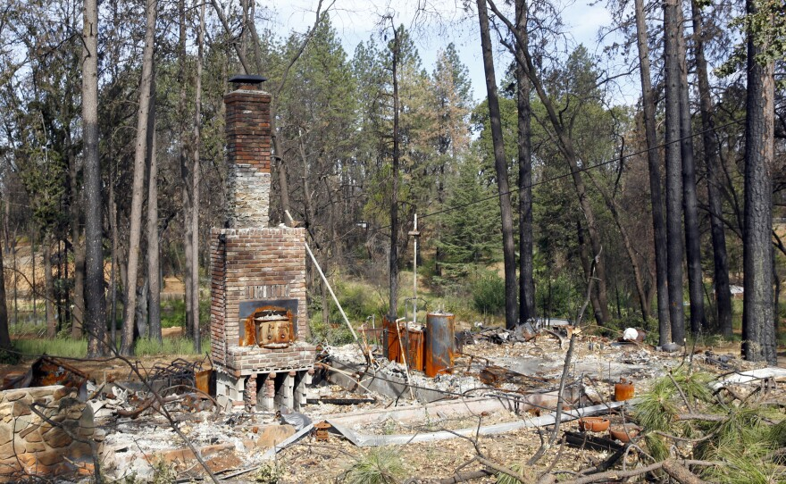 In this Aug. 21, 2019, file photo, burned trees surround the burned-out remains of a home destroyed by the 2018 Camp Fire in Paradise, Calif.