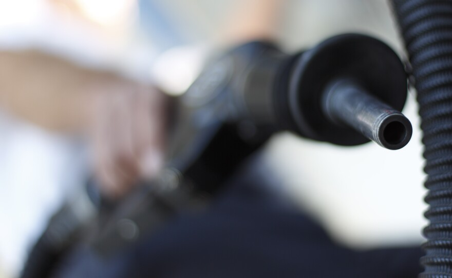 A San Diego gas station worker poses holding a gas nozzle, March 9, 2011.