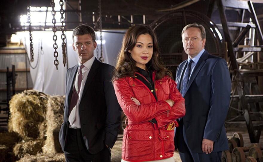 "Jason Hughes (as DS Benjamin Jones), Natalie Mendoza (as Sasha Fleetwood in ""The Dark Rider""), and Neil Dudgeon (as DCI John Barnaby) on MIDSOMER MURDERS Season 15."