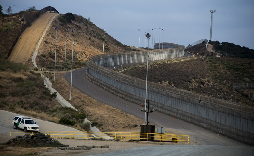 """A section of secondary fencing, covered with concertina wire at the base and top of the structure, snakes along a winding road near the San Ysidro Port of Entry in San Diego on Aug. 16, 2017. Also shown is a line of primary fencing made of corrugated steel, left, a Border Patrol vehicle along a drainage area and a tower with """"virtual fencing"""" technology at the top of the hill."""